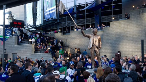 Fans crowd around a statue honoring former Vancouver Canucks' assistant coach Roger Neilson after it was unveiled in Vancouver, B.C., on Thursday April 7, 2011. THE CANADIAN PRESS/Darryl Dyck