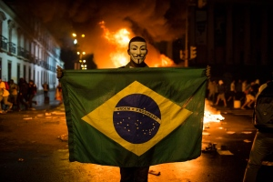 A demonstrator holds a Brazilian flag in front of a burning barricade during a protest in Rio de Janeiro, Brazil, Monday, June 17, 2013. (AP / Felipe Dana)