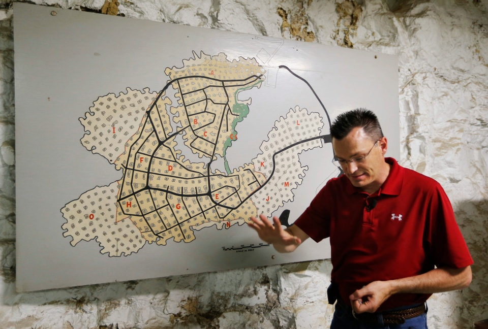 Coby Cullins stands next to a map of the Vivos Shelter and Resort during a tour of the facility in Atchison, Kan., on June 18, 2013. (AP Photo/Orlin Wagner)