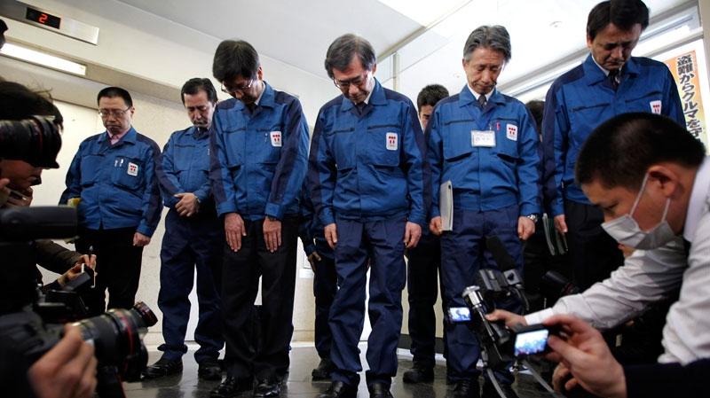 Tokyo Electric Power Co. President Masataka Shimizu, third right, and other TEPCO officials observe a minute of silence at the Fukushima Prefectural Office in Fukushima, Monday, April 11, 2011. (AP / Hiro Komae)