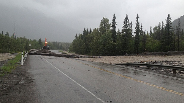 Highway 1A is covered with debris after a mudslide to excessive rains overnight on Wednesday. Traffic on Highway 1 is still shut down east and west of Canmore.
