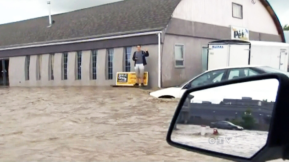 A man surrounded by floodwaters waves to a passing vehicle in High River, Alta. Thursday, June 20, 2013.