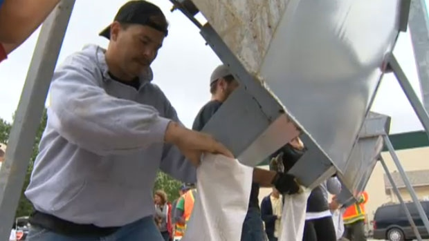 Volunteers help fill sandbags in High River to protect homes and businesses from the rising waters of the Highwood River.