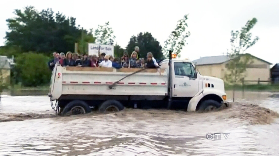 A local garbage truck drives through floodwaters while evacuating a group of residents in High River, Alta. Thursday, June 20, 2013.