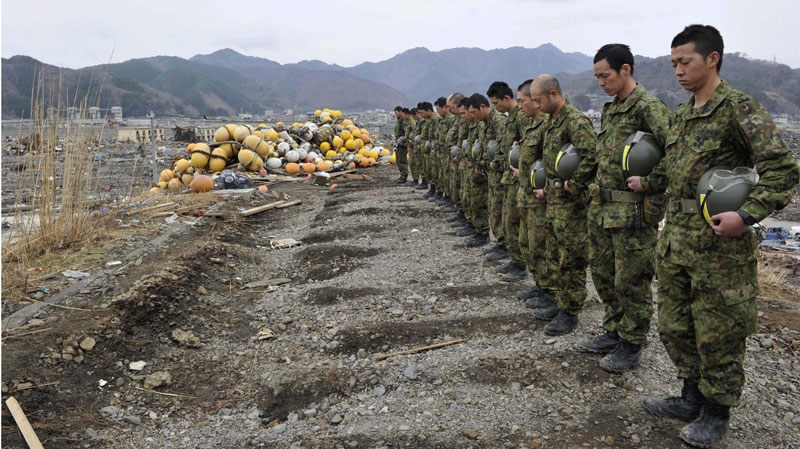 Japan's Ground Self-Defense Force members take a moment of silence exactly a month after a massive earthquake struck the area in Otsuchi, Iwate Prefecture, Monday, April 11, 2011. (AP / Yomiuri Shimbun, Yasuhiro Takami)