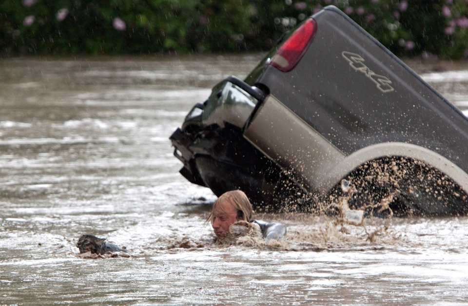 Kevan Yaets swims after his cat Momo as the floodwaters sweep him downstream and submerge the cab of his truck in High River, Alta. on June 20, 2013. (Jordan Verlage / THE CANADIAN PRESS)