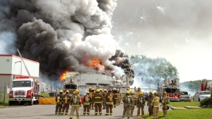Firefighters gather at the scene of an explosion at the B.E.M. fireworks factory Thursday, June 20, 2013 in Coteau-du-Lac, Que. ( Stephane Brunet / THE CANADIAN PRESS)