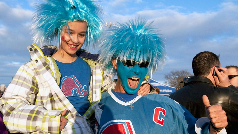 Nordiques fans Andre and Marie-Felix Poirier celebrate outside the Pepsi Colisee as approximately 15,000 people bought tickets to watch the Montreal Canadiens vs Atlanta Trashers on giant screens in Quebec City, Tuesday, March 29, 2011. (Jacques Boissinot / THE CANADIAN PRESS)