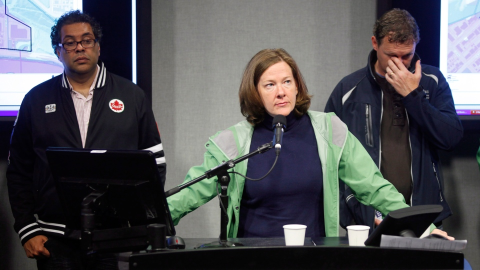 Alberta Premier Alison Redford, centre, addresses the media as Calgary Mayor Naheed Nenshi, left, and Alberta Municipal Affairs Minister Doug Griffiths look on during a press conference in Calgary, Alta., Friday, June 21, 2013. (Jeff McIntosh / THE CANADIAN PRESS)