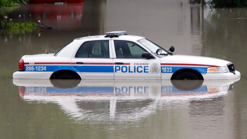 A police car sits stuck in a parking lot of an apartment building after heavy rains have caused flooding, closed roads, and forced evacuation in Calgary, Friday, June 21, 2013. (Jeff McIntosh / THE CANADIAN PRESS)