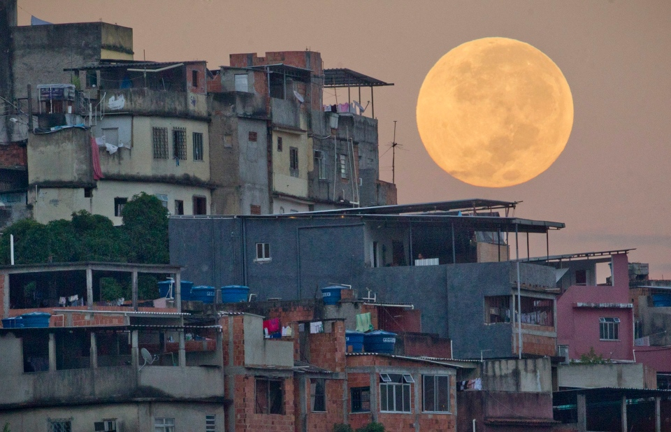 The 'supermoon' appears behind the Mare shanty town complex in Rio de Janeiro, Sunday, May 6, 2012.  (AP / Victor R. Caivano)