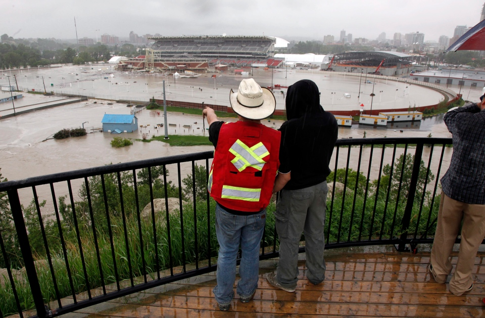 Calgarians look out over a flooded Calgary Stampede grounds and Saddledome in Calgary, Friday, June 21, 2013. (Jeff McIntosh / THE CANADIAN PRESS)