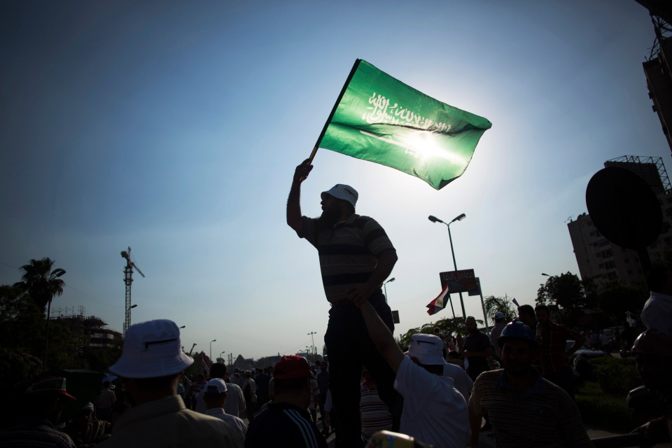 An Egyptian man waves an Islamic flag during a rally supporting Islamist President Mohammed Morsi in Cairo, Egypt, Friday, June 21, 2013. Supporters of Egypt's Islamist president rallied in a massive demonstration Friday in a show of force against opponents demanding his ouster amid increasing tension and polarization in the country. Demonstrators gathered in a main boulevard near Cairo's presidential palace, many with their fists raised, carrying pictures of President Mohammed Morsi and chanting religious slogans. (AP Photo/Manu Brabo)