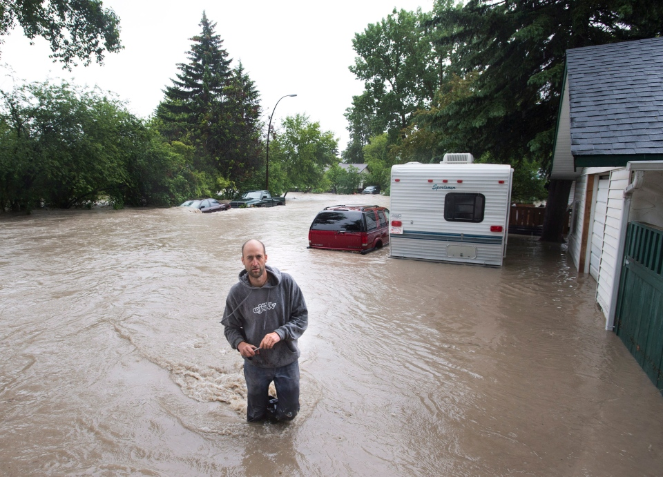 A resident walks through a alley as he tries to make it to her home in the flooded community of Bowness as up to 100,000 people have been evacuated from their homes in Calgary, on Friday, June 21, 2013. (Nathan Denette / THE CANADIAN PRESS)