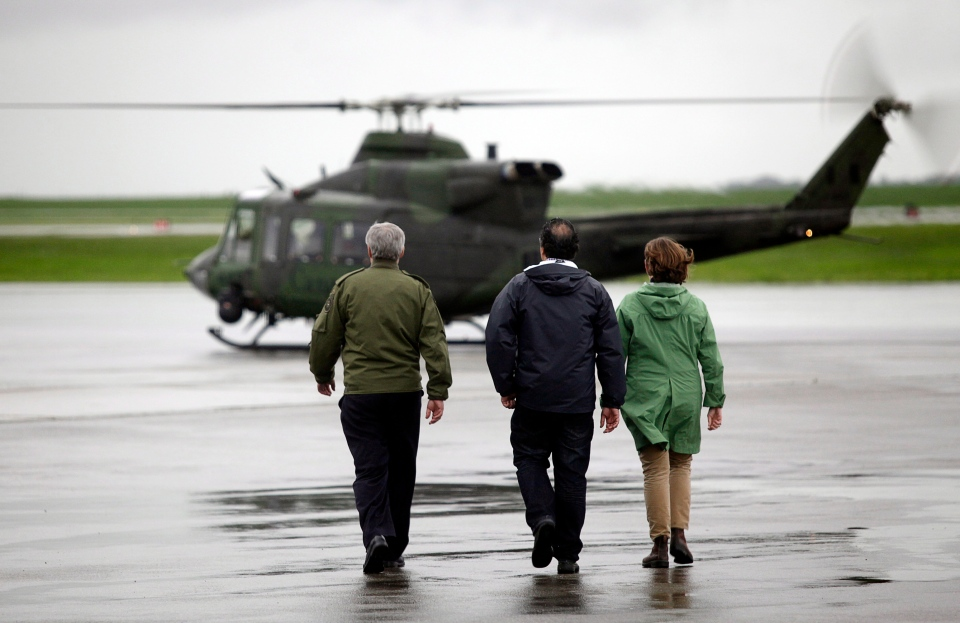 Prime Minister Stephen Harper, left, walks to a waiting helicopter with Alberta Premier Alison Redford, right, and Calgary Mayor Naheed Nenshi, for an aerial tour of flooding in Calgary, Friday, June 21, 2013. (Jeff McIntosh / THE CANADIAN PRESS)