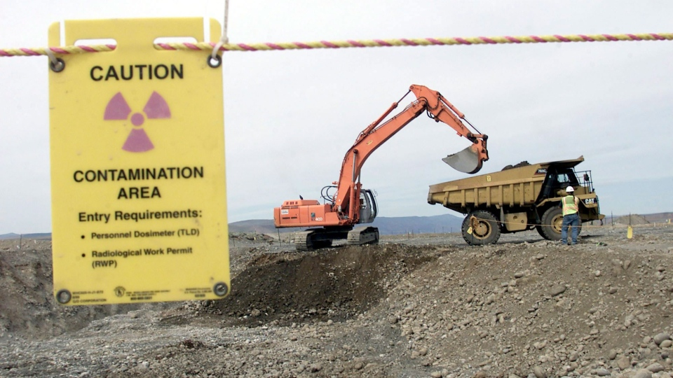 Workers use heavy machinery to remove waste in an area near two dormant nuclear reactors on the Hanford Nuclear Reservation near Richland, Wash., May 6, 2004. (AP / Jackie Johnston)