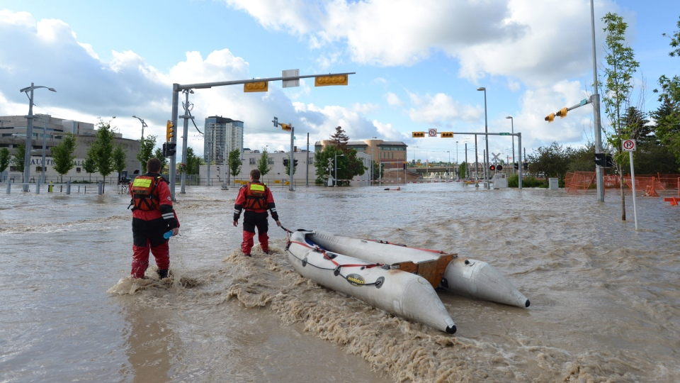 Rescue workers pull a rubber boat as they walk in the flooded streets of Calgary on Friday June 21, 2013. (Jonathan Hayward / THE CANADIAN PRESS)