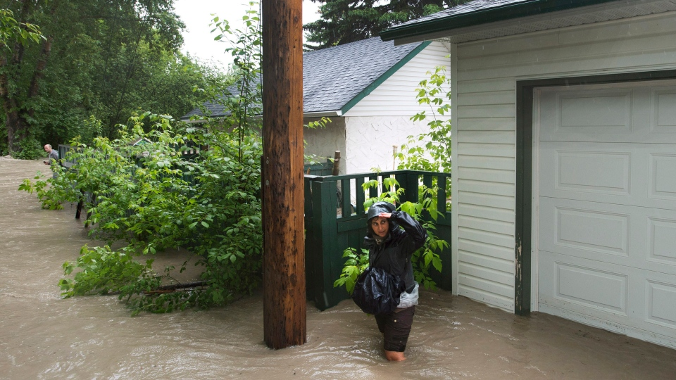A resident walks through a alley as she tries to make it to her home in the flooded community of Bowness as up to 100,000 people have been evacuated from their homes in Calgary, Alta., on Friday, June 21, 2013. (Nathan Denette / THE CANADIAN PRESS)