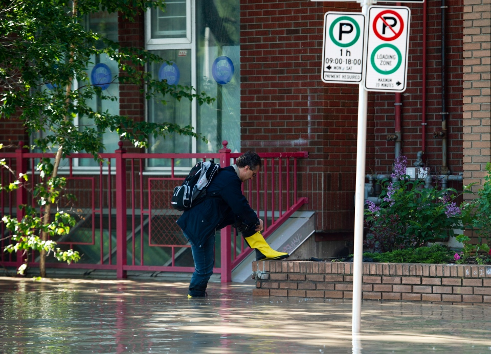A man adjusts his rubber boots as he walks through a flooded Chinatown in downtown Calgary as up to 75,000 people have been evacuated from their homes in Calgary, on Saturday, June 22, 2013. (Nathan Denette / THE CANADIAN PRESS)