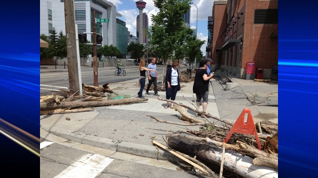 People standing near a field of debris at the intersection of 15 Ave. and 1 St.  S.E.