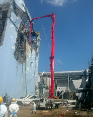 In this photo released by Tokyo Electric Power Co., workers operate a modified Putzmeister 70Z, the world's largest concrete pump mounted on a truck, to pump contaminated water from the Unit 4 at the tsunami-damaged Fukushima Dai-ichi nuclear power plant in Okumamachi, Fukushima Prefecture, northeastern Japan, Tuesday, April 12, 2011. (Tokyo Electric Power Co.)