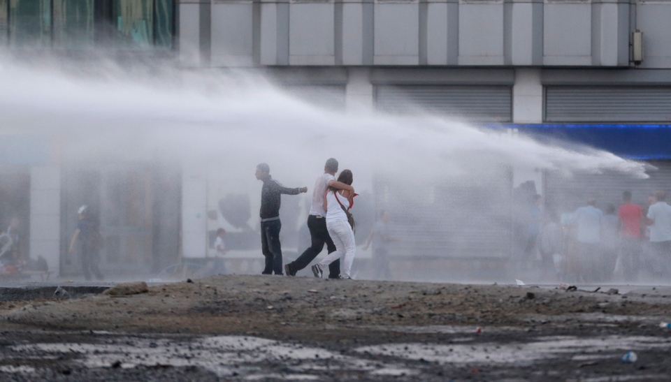 Protesters are sprayed with water canon during clashes with riot police in Istanbul, Turkey, Saturday, June 22, 2013. (AP Photo/Petr David Josek)