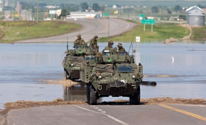 A convoy of military vehicles makes its way through a flooded highway before heading in to the flood zone in High River, Alta. on Saturday June 22, 2013 after the Highwood River overflowed its banks. (Jordan Verlage / THE CANADIAN PRESS)