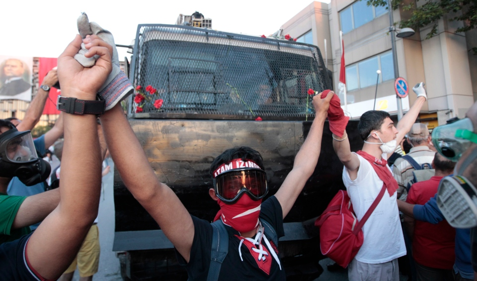 Protesters try to block a water canon truck during a demonstration at Taksim Square in Istanbul, Turkey, Saturday, June 22, 2013. (AP Photo/Petr David Josek)