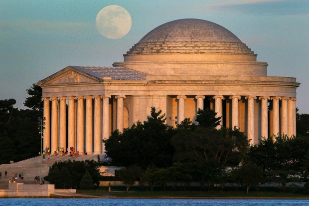 A full moon rises behind the Jefferson Memorial