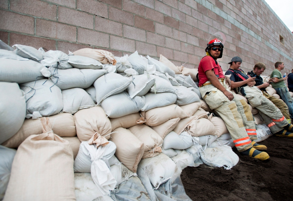 Volunteer firefighters and take a break after building up a wall of sand bags in preparation for flooding in Medicine Hat, Alta., on Saturday, June 22, 2013. (Nathan Denette / THE CANADIAN PRESS)
