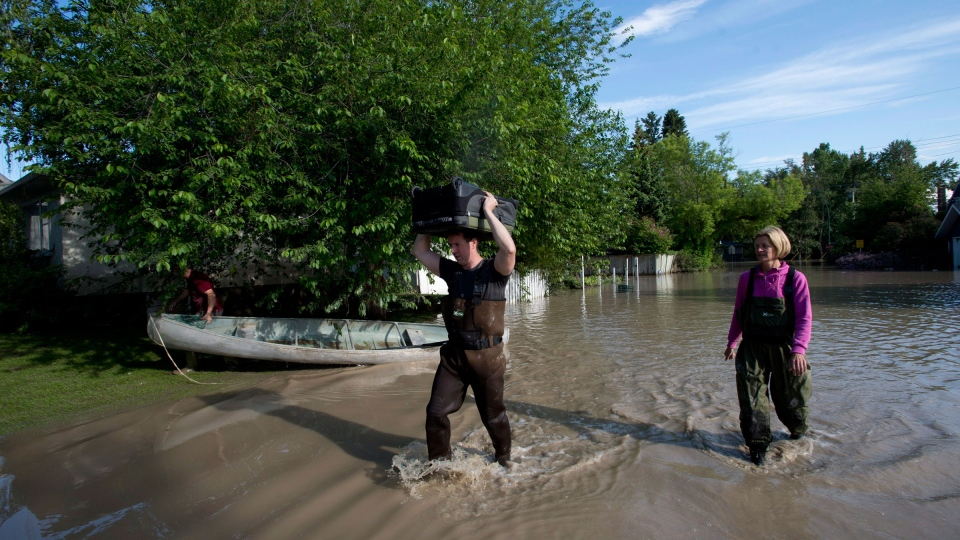 Nathan and Sarah MacBey carry a suitcase of clean dry clothes from their home after the waters receded in Calgary's south end, Saturday, June 22, 2013. (Jonathan Hayward / THE CANADIAN PRESS)