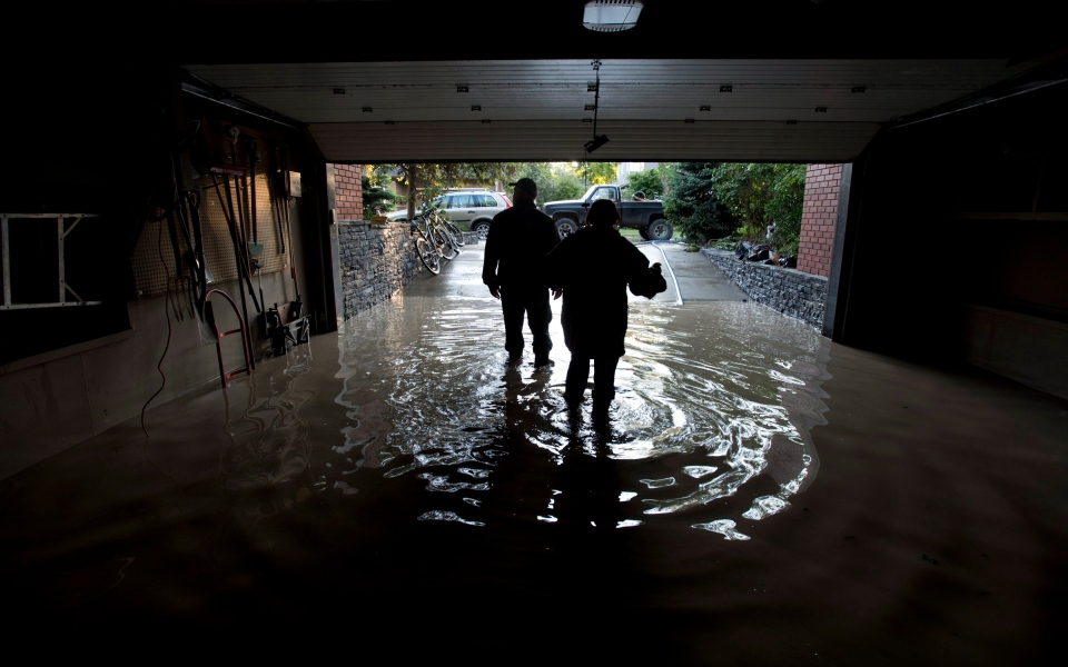 A couple is silhouetted as they walk out of their flooded garage near the Elbow River in Calgary on Saturday, June 22, 2013. (Jonathan Hayward / THE CANADIAN PRESS)