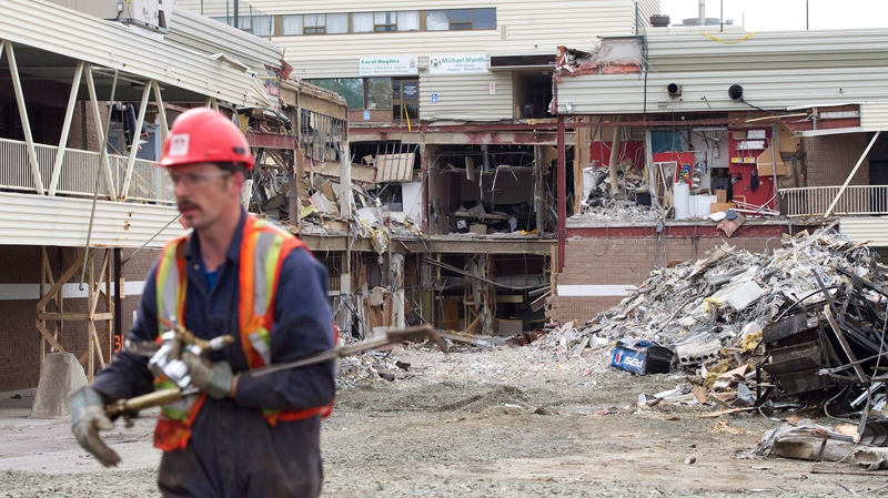 A worker walks back from the rubble after Ontario Premier Dalton McGuinty speaks to the community of Elliot lake regarding the recovery of two bodies at the Algo Centre Mall in Elliot Lake, Ont., on June 27, 2012. (Nathan Denette / THE CANADIAN PRESS)