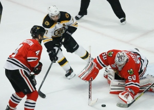 Boston Bruins centre Patrice Bergeron (37) looks to score against Chicago Blackhawks goalie Corey Crawford (50) in the first period during Game 5 of the NHL hockey Stanley Cup Finals on June 22, 2013 in Chicago. Bergeron left the game with an injury in the second period and did not return. (AP Photo/Nam Y. Huh)