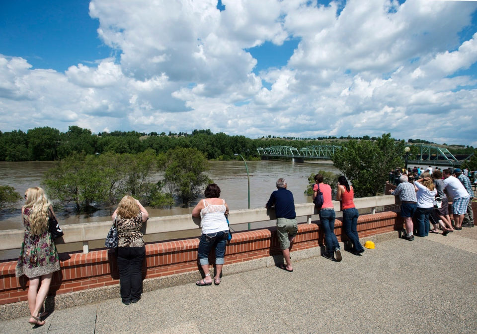 People watch as the South Saskatchewan River rises rapidly and begins flooding in Medicine Hat, Alta., on Sunday, June 23, 2013. (Nathan Denette / THE CANADIAN PRESS)