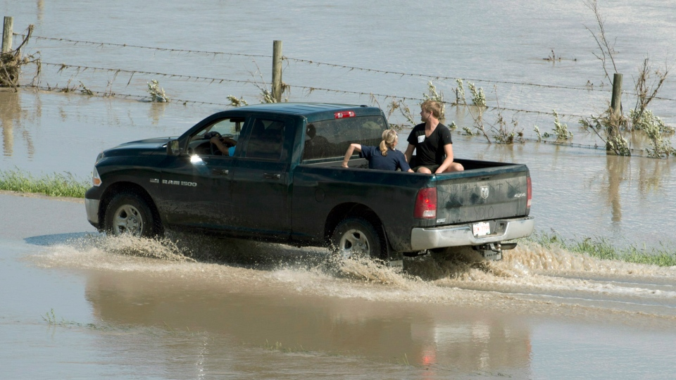 A truck drives down a flooded road on the Siksika First Nation, Alta., on Sunday, June 23, 2013. (Jonathan Hayward / THE CANADIAN PRESS)
