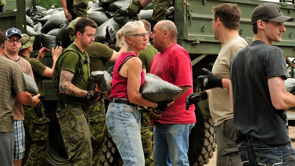Canadian Forces members assist Medicine Hat residents to pile sandbags to create a retaining wall around the city's water treatment facility. (Master Cpl Patrick Blanchard / Canadian Forces Combat Camera)
