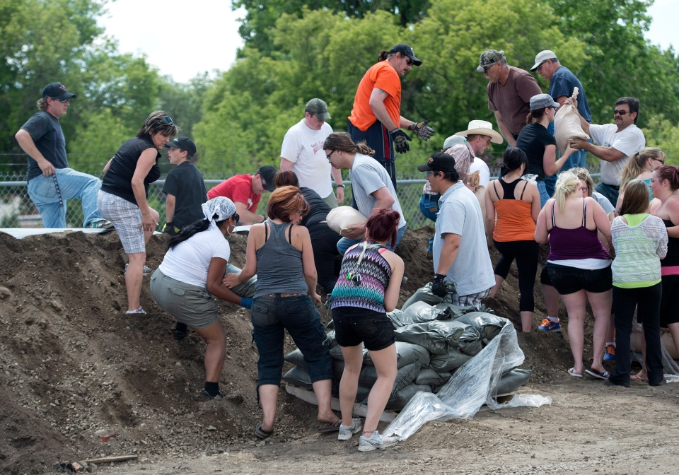 People place sand bags as the river rises rapidly and begins flooding in Medicine Hat, Alta., on Sunday, June 23, 2013. (Nathan Denette / THE CANADIAN PRESS)