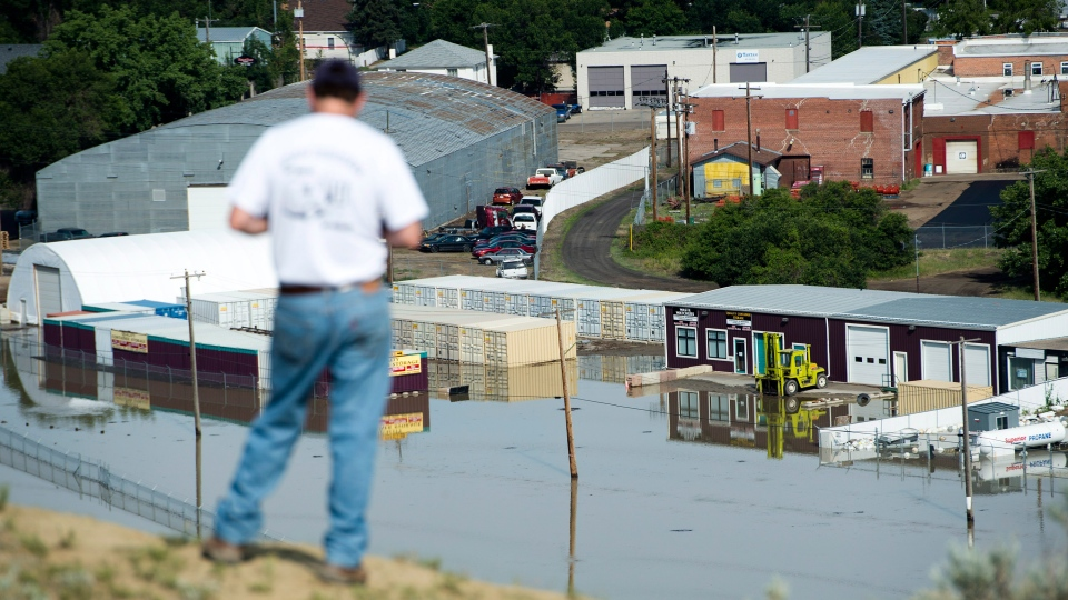 A man looks over flooded businesses after the South Saskatchewan River peaked in Medicine Hat, Alta., on Monday, June 24, 2013. (Nathan Denette / THE CANADIAN PRESS)