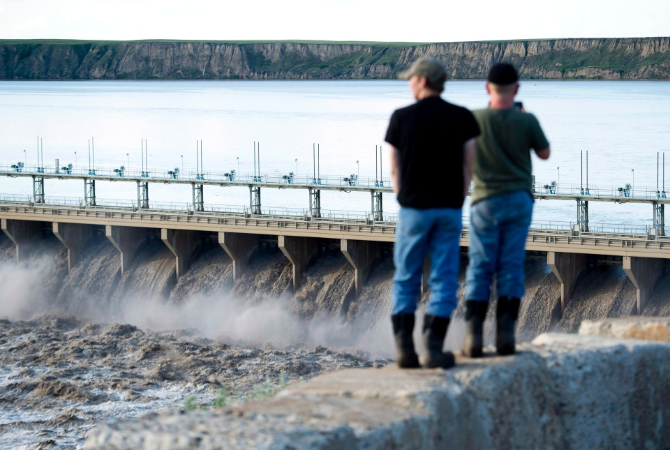 People watch as the Bassano Dam takes on water from the Bow River before meeting up with the South Saskatchewan River in Bassano, Alta. on Saturday, June 22, 2013. (Nathan Denette / THE CANADIAN PRESS)