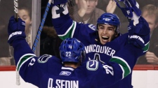 Vancouver Canucks' Alex Burrows, right, and Daniel Sedin, of Sweden, celebrate Burrows' goal against the Colorado Avalanche during third period NHL hockey game action in Vancouver, B.C., on Wednesday November 24, 2010. THE CANADIAN PRESS/Darryl Dyck