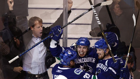 Vancouver Canucks' Henrik Sedin, of Sweden, from left, Alex Burrows and Daniel Sedin, of Sweden, celebrate Burrows' goal against the Colorado Avalanche during third period NHL hockey game action in Vancouver, B.C., on Wednesday November 24, 2010. THE CANADIAN PRESS/Darryl Dyck