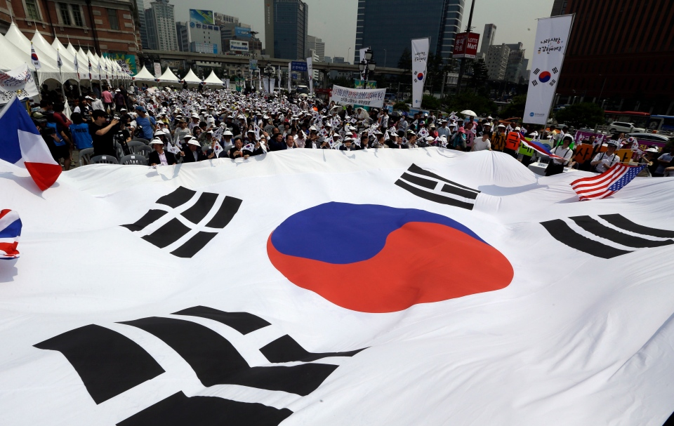 Members of Korea Freedom Federation carry a huge national flag during a ceremony to mark the 63rd anniversary of the outbreak of the Korean War in Seoul, South Korea, Tuesday, June 25, 2013. (AP / Lee Jin-man)