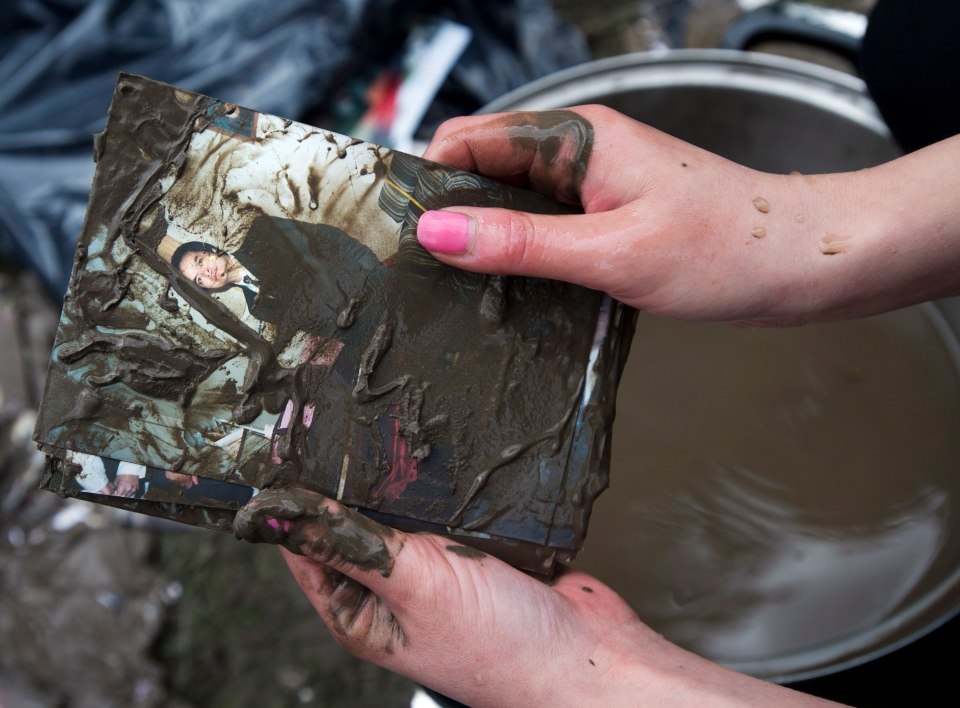 Resident Lisa Nguyen cleans the mud from a photograph of her father as she and volunteers are in clean up mode in the community of Bowness in Calgary, Monday, June 24, 2013. (Nathan Denette / THE CANADIAN PRESS)