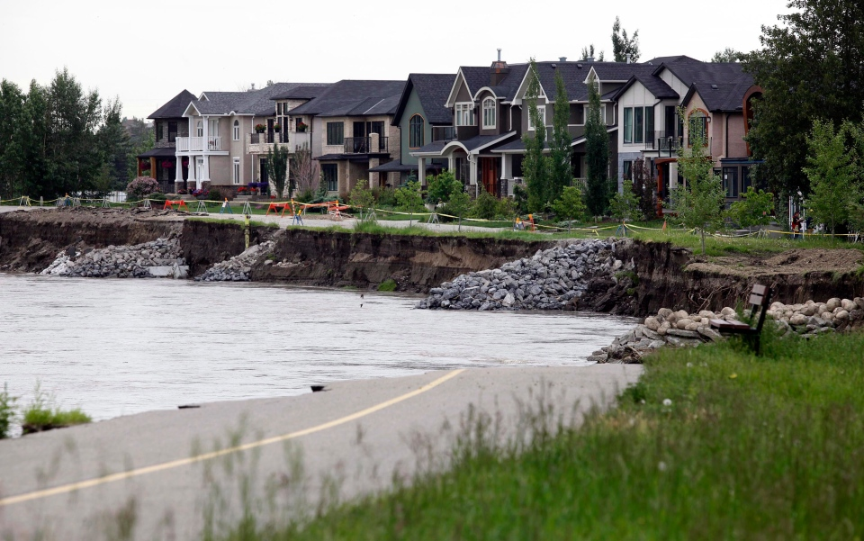 A bike path that used to lead to a green space now stops abruptly at the banks of the Bow River in the Inglewood neighborhood as clean-up continues in Calgary, Alta., Tuesday, June 25, 2013. (Jeff McIntosh / THE CANADIAN PRESS)