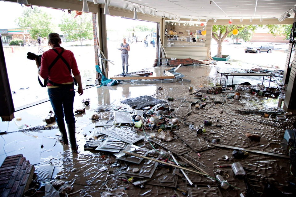 Photographers take photos of destroyed downtown shops in High River, Alta. on Saturday, June 22, 2013. (Jordan Verlage/The Canadian Press)