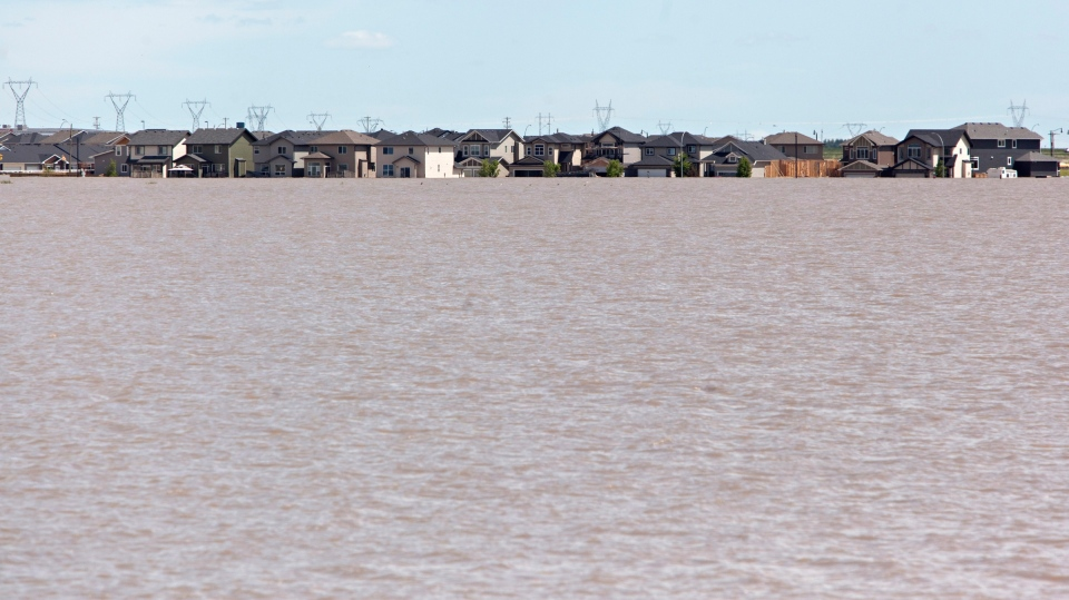 Houses sit at the edge of a large lake caused by floodwaters in High River, Alberta on Tuesday, June 25, 2013. (Jordan Verlag / THE CANADIAN PRESS)