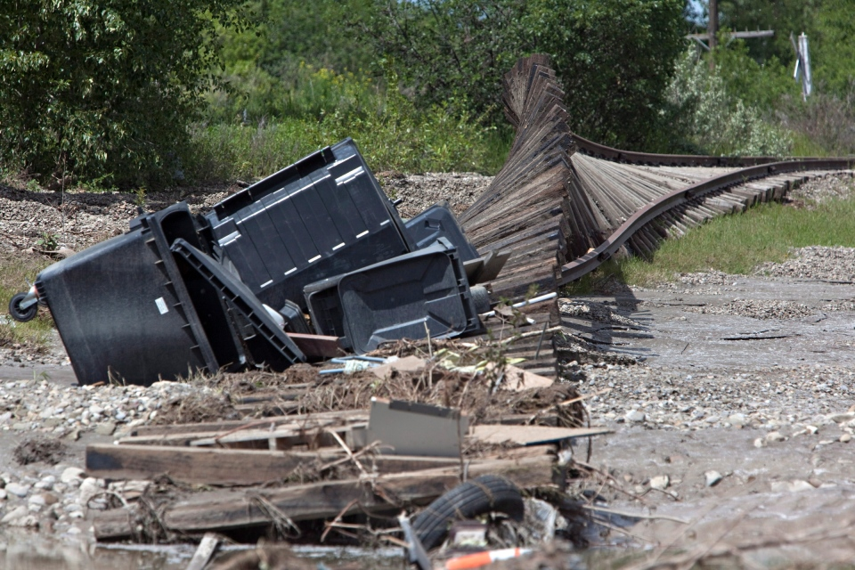 Train tracks lay curled over themselves from rushing flood waters in High River, Alberta on Tuesday, June 25, 2013. (Jordan Verlage / THE CANADIAN PRESS)