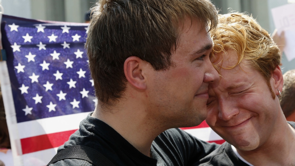 Michael Knaapen, left, and his husband John Becker, right, embrace outside the Supreme Court in Washington, Wednesday, June 26, 2013. (AP / Charles Dharapak)