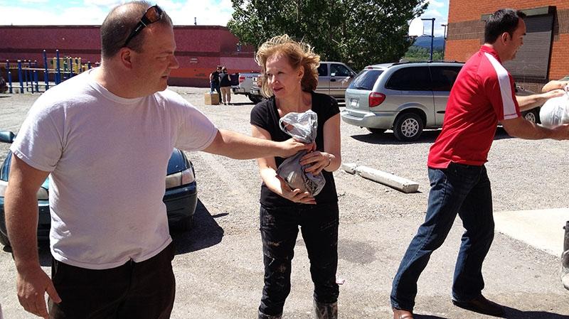 Lauren Harper is lending a helping hand by unloading trucks in Morley, Alta., on Wednesday, June 26, 2013. (Darin Saarela \ CTV News)